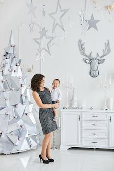 Mulher jovem e linda em um vestido da moda posando com seu filho fofo no interior decorado para o natal