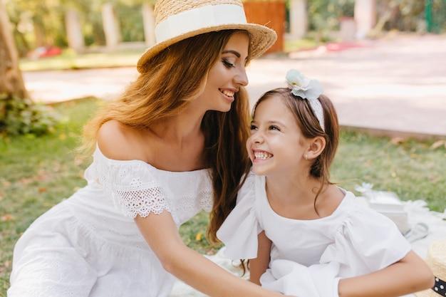 Mulher jovem e linda no chapéu da moda com fita branca vai beijar a filha na testa. rindo menina de cabelos escuros com fita se divertindo com a mãe, passando o fim de semana no parque.