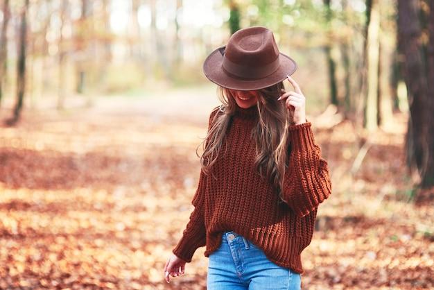 Mulher jovem e linda usando roupas quentes na floresta de outono