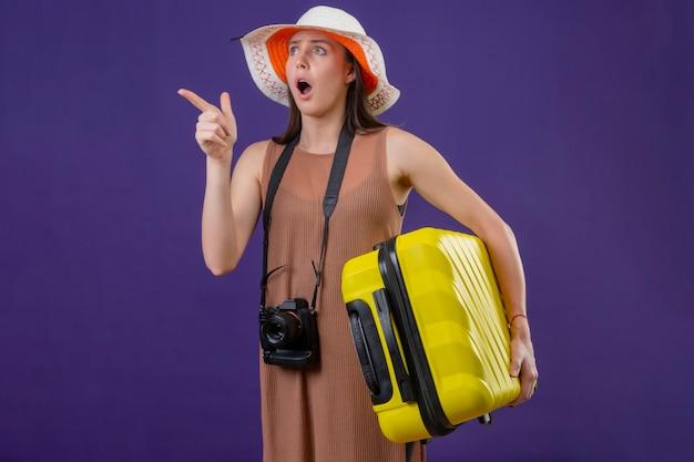 Mulher jovem e linda viajante com chapéu de verão com mala amarela e câmera apontando para algo parecendo com expressão de medo espantada de pé sobre um fundo roxo