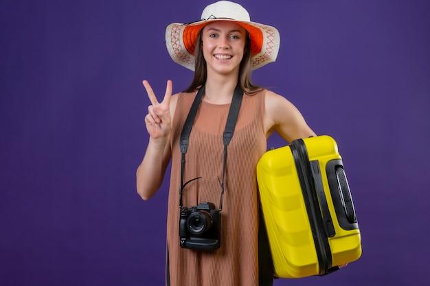 Mulher jovem e linda viajante com chapéu de verão com mala amarela e câmera positiva e feliz sorrindo alegremente mostrando o sinal da vitória ou número dois em pé sobre fundo roxo