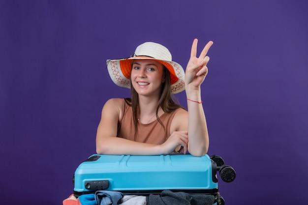 Mulher jovem e linda viajante com chapéu de verão com mala cheia de roupas, positiva e feliz, sorrindo alegremente otimista, mostrando o sinal da vitória ou número dois em pé sobre um fundo roxo