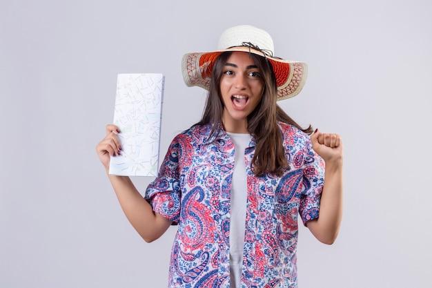 Mulher jovem e linda viajante com chapéu de verão segurando um mapa, parecendo animada e feliz levantando o punho após uma vitória em pé sobre um fundo branco