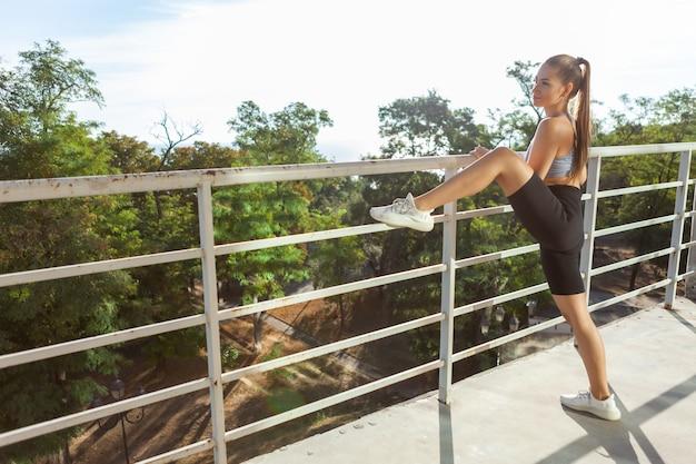 Mulher jovem e magra fazendo exercícios ao ar livre