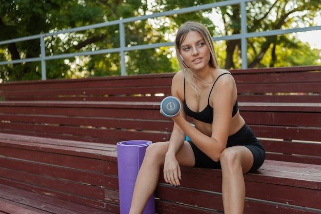 Mulher jovem e magra fazendo exercícios com halteres enquanto está sentada na tribuna de madeira ao ar livre pela manhã