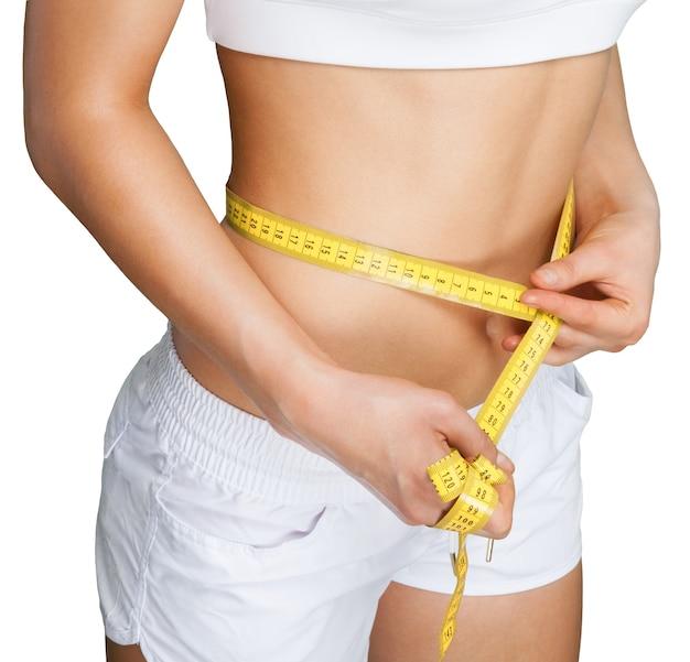 Mulher jovem e magra medindo a cintura fina com uma fita métrica, close-up
