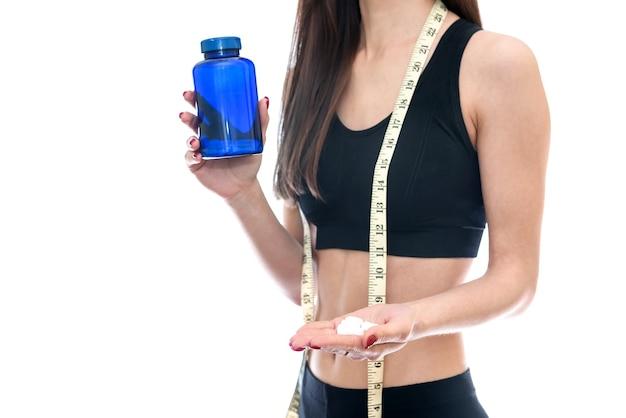 Mulher jovem e magra oferecendo comprimidos do frasco