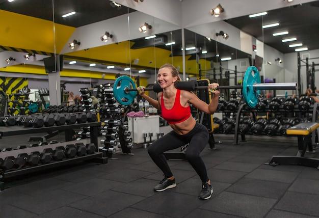 Mulher jovem e magra praticando agachamento com uma barra sobre os ombros em uma academia moderna
