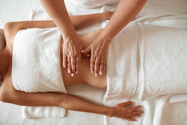 Mulher jovem e magra recebendo massagem estomacal em salão de spa
