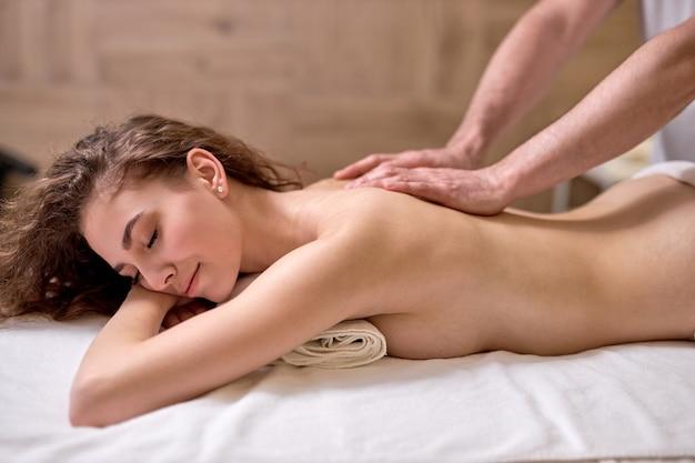 Mulher jovem e magra relaxada recebendo massagem de corpo inteiro em vista lateral do spa moderno