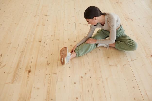 Mulher jovem e magra sentada no chão esticando as pernas durante o treinamento na academia