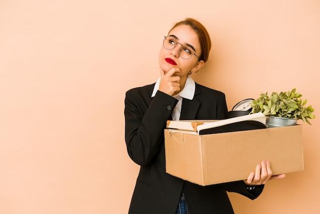 Mulher jovem e magrela de negócios árabes movendo-se para um emprego isolado, olhando de lado com expressão duvidosa e cética