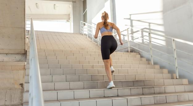 Mulher jovem e magro sobe as escadas correndo. treino urbano