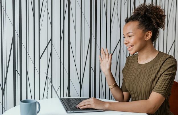 Mulher jovem e moderna trabalhando em casa em seu laptop