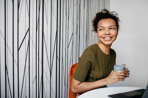 Mulher jovem e moderna trabalhando em casa