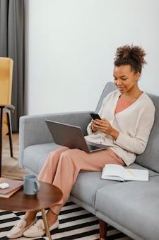 Mulher jovem e moderna trabalhando enquanto está sentada no sofá