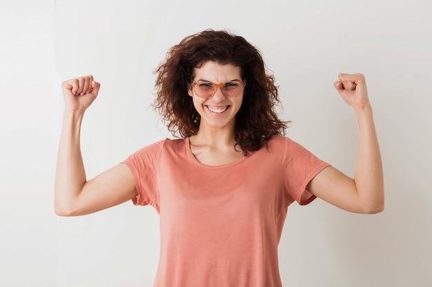 Mulher jovem e muito elegante de óculos, segurando as mãos em gesto de vitória, músculos fortes, emocional, vencedor, cabelo encaracolado, sorrindo, emoção positiva, feliz, isolada, camiseta rosa, estilo moderno