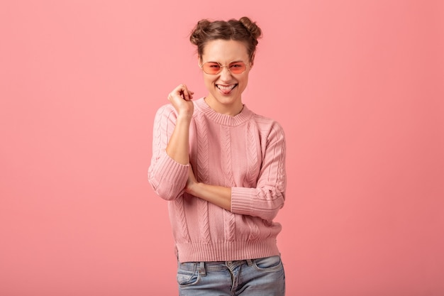 Mulher jovem e muito sorridente com uma expressão de rosto engraçada, mostrando a língua em um suéter rosa e óculos de sol isolados no fundo rosa do estúdio