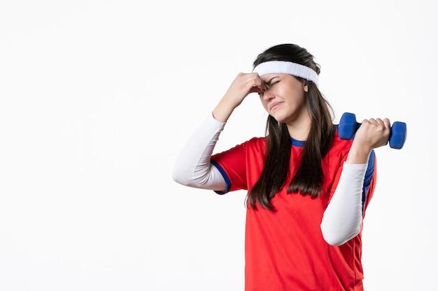 Mulher jovem e nervosa de frente com roupas esportivas e halteres azuis