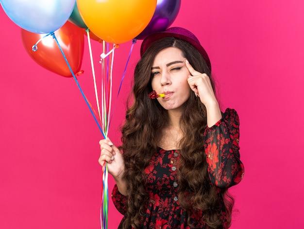 Mulher jovem e pensativa com um chapéu de festa, segurando balões, soprando a buzina de festa, olhando para frente fazendo um gesto de pensar com um olho fechado, isolado na parede rosa