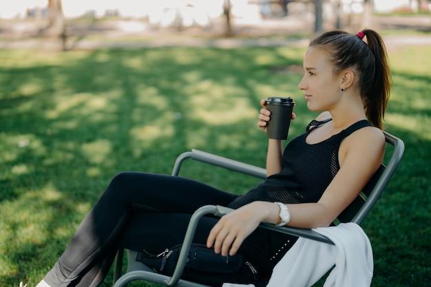 Mulher jovem e pensativa e esportiva com rabo de cavalo faz uma pausa para o café após o treinamento em poses em uma cadeira confortável com uma bebida quente no parque contra a grama verde aprecia um dia ensolarado concentrado na distância