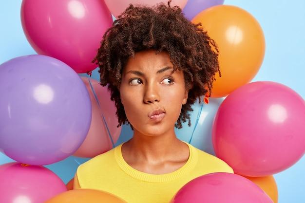 Mulher jovem e pensativa posando rodeada de balões coloridos de aniversário
