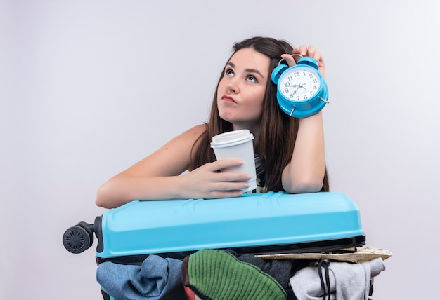 Mulher jovem e pensativa viajante segurando o despertador e viajando com uma xícara de café de plástico com mala na parede branca isolada
