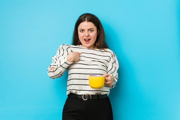 Mulher jovem e plus size segurando uma caneca de chá surpresa, apontando para si mesmo, sorrindo amplamente.
