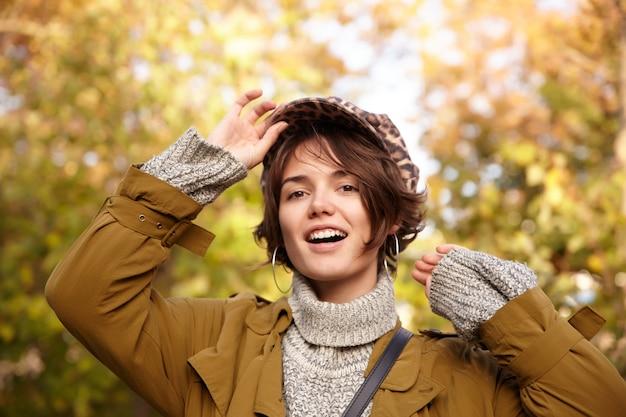Mulher jovem e positiva, bonita morena de olhos castanhos, com penteado bob, mantendo o boné com a mão levantada enquanto olha, vestindo roupas quentes e elegantes enquanto caminha pelo parque