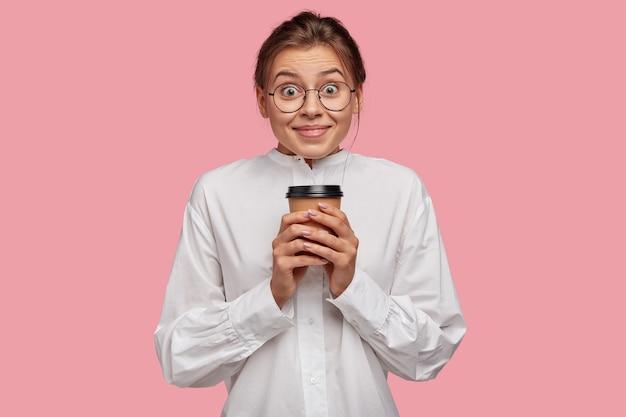 Mulher jovem e positiva com óculos posando contra a parede rosa