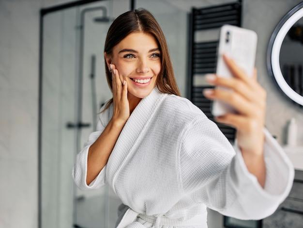 Mulher jovem e positiva em um roupão de banho tirando uma selfie