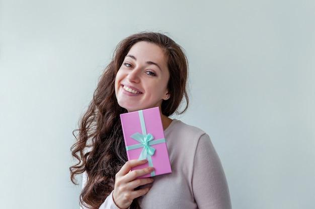 Mulher jovem e positiva segurando uma pequena caixa de presente rosa isolada no branco