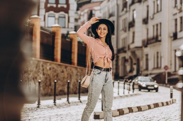 Mulher jovem e positiva tocando seu chapéu na rua e desviando o olhar com um sorriso