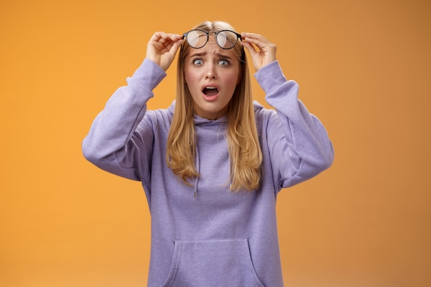 Mulher jovem e preocupada chocada procurando estudante arruinar trabalho olhando perturbado óculos de decolagem estourando olhos arregalados, câmera ofegante, mudo, terrível acidente aconteceu, fundo laranja.