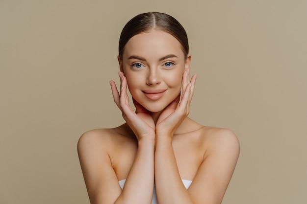 Mulher jovem e renovada e satisfeita toca o rosto suavemente, tem pele limpa e saudável, usa maquiagem mínima
