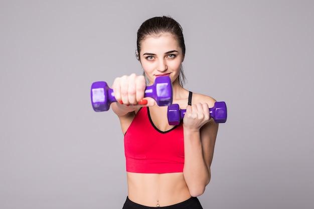 Mulher jovem e saudável com halteres malhando isolado na parede branca. conceito de ginásio de fitness