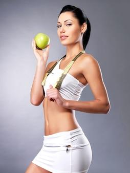 Mulher jovem e saudável com maçã após a dieta. mulher esportiva com figura perfeita