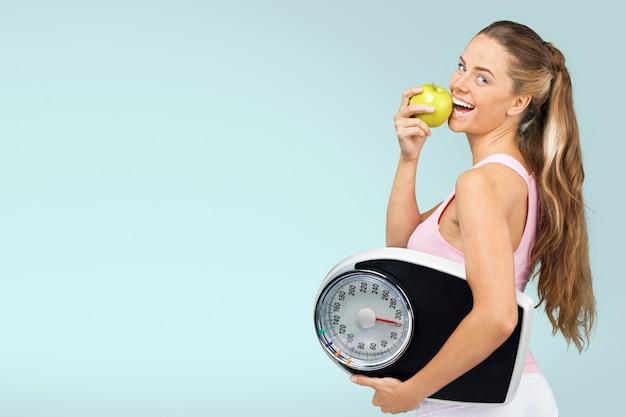 Mulher jovem e saudável com maçã e escamas isoladas