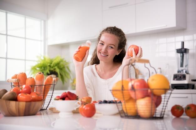 Mulher jovem e saudável em uma cozinha com frutas, vegetais e suco