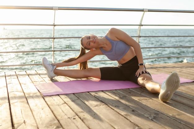 Mulher jovem e saudável fazendo alongamento de pernas antes do treino enquanto está sentada na esteira ao nascer do sol na praia