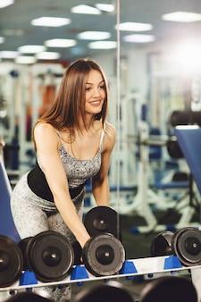Mulher jovem e saudável fazendo exercícios com halteres e poses na frente do espelho do ginásio