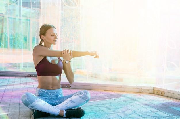 Mulher jovem e saudável no sportswear, esticando a mão dela durante o exercício na ponte