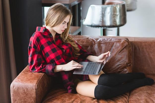 Mulher jovem e sedutora pensativa com camisa quadriculada e meias pretas, trabalhando com o laptop no sofá de couro em casa