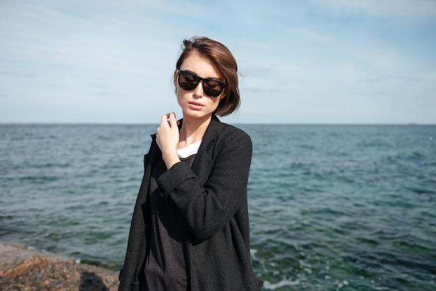 Mulher jovem e sensual com óculos escuros em pé perto do mar
