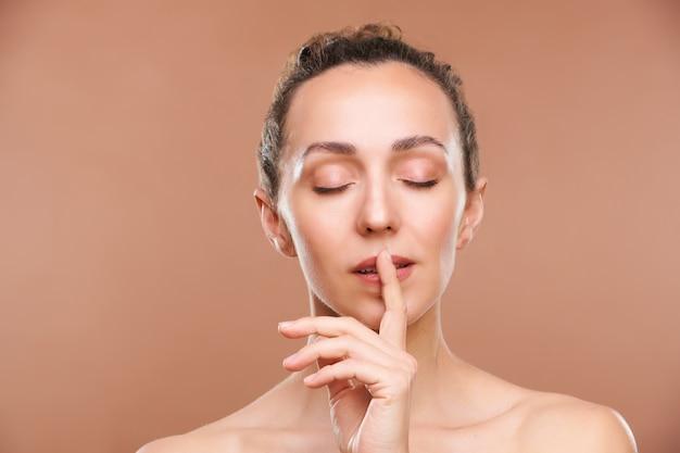 Mulher jovem e serena com o dedo indicador na boca e olhos fechados fazendo um gesto de shh
