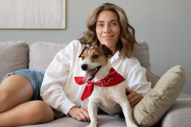 Mulher jovem e seu cachorro no sofá em casa. adorável animal de estimação. animal doméstico