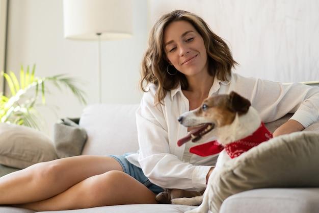 Mulher jovem e seu cachorro no sofá em casa. adorável animal de estimação.