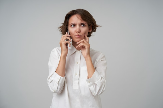Mulher jovem e severa, morena com penteado casual, tendo uma chamada importante e olhando pensativamente de lado, mantendo o dedo indicador na bochecha enquanto posa