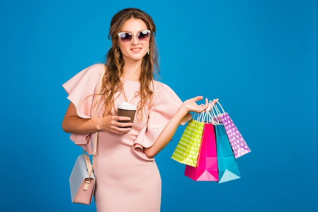 Mulher jovem e sexy elegante em um vestido de luxo rosa, tendência da moda de verão, estilo chique, óculos de sol, fundo de estúdio azul, compras, segurando sacolas de papel, bebendo café, shopaholic