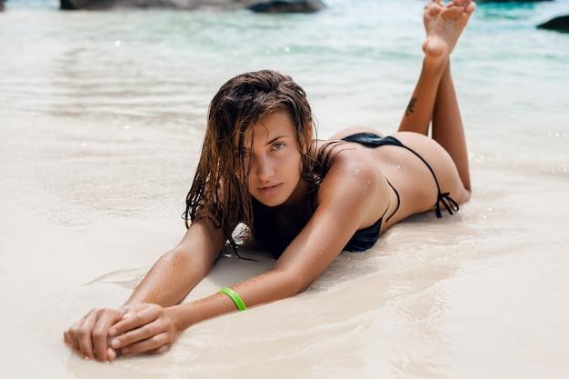 Mulher jovem e sexy esguia, corpo lindo e perfeito, pele bronzeada, maiô de biquíni preto, banho de sol, mar, férias de verão na ásia, sensual, quente, viajar na tailândia, praia tropical, ilhas similan